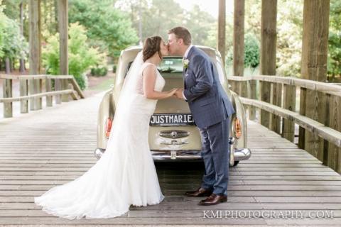 bride and groom kissing at river landing